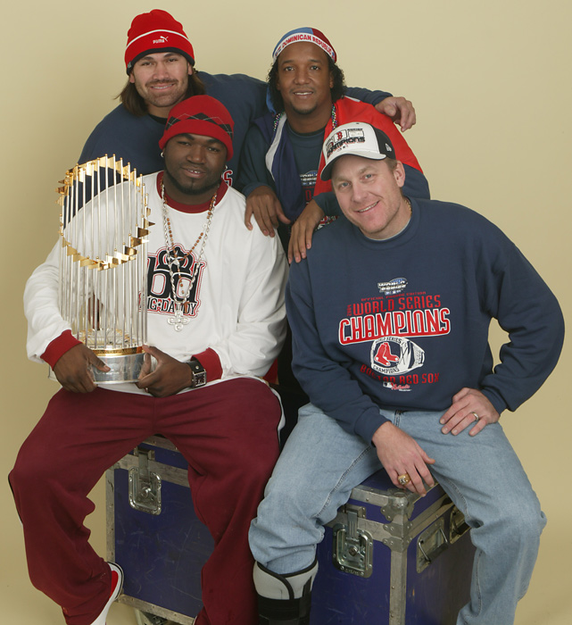 Four of the prominent members -- Johnny Damon, Pedro Martinez, Ortiz and Curt Schilling -- of the 2004 World Champion Red Sox chill on top of a box with the World Series Trophy.