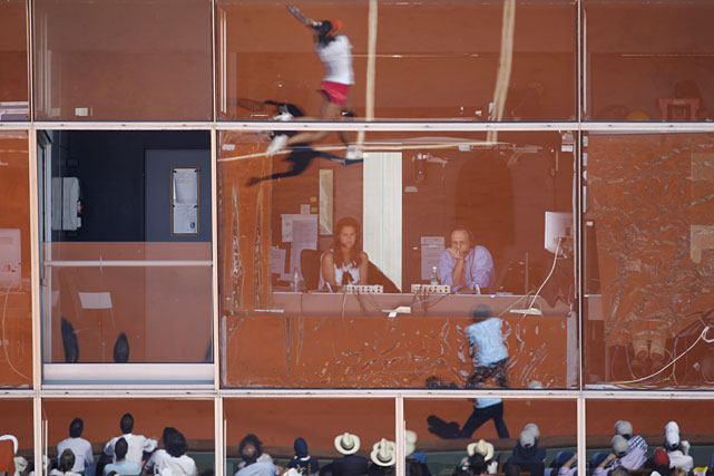 Li Na (top) is reflected in the windows of the TV commentary booth during Thursday's first women's semifinal.