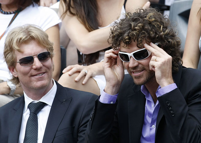 Former French Open champions Jim Courier (left) and Gustavo Kuerten (right) joke before Sunday's Nadal-Federer match.