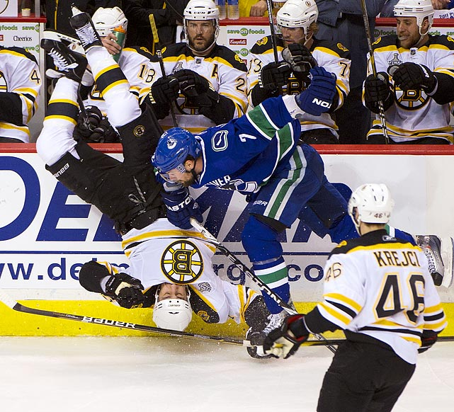 Canucks defenseman Dan Hamhuis flips Bruins leftwinger Milan Lucic in front of the Bruins' bench during the Canucks' 1-0 victory in Game 1 of the Stanley Cup finals. Hamhuis would leave Game 1 with an undisclosed injury.