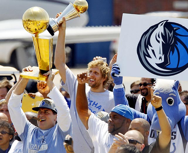 Dallas Mavericks owner Mark Cuban (left) hoists the Larry O'Brien trophy as the Dallas Mavericks return to their home city a day after winning the NBA finals. Cuban claimed he slept alongside the trophy on Sunday night.