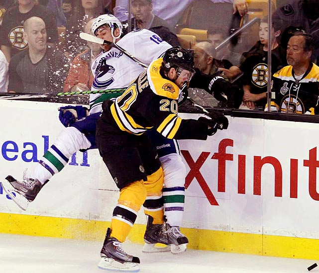 Boston Bruins leftwinger Daniel Paille slams Vancouver Canucks defenseman Christopher Tanev into the boards during the Bruins' 5-2 win in Game 6 of the Stanley Cup finals.