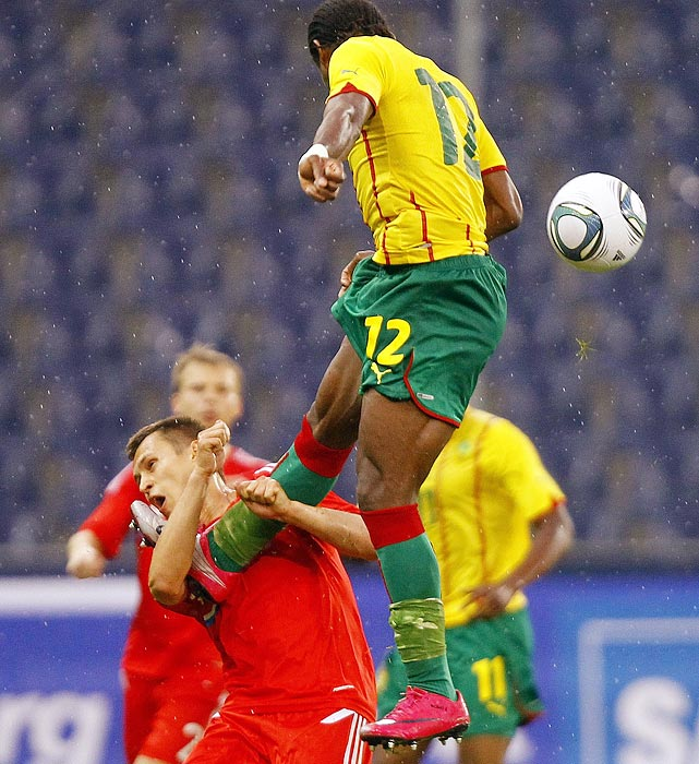 Cameroon's Henri Bedimo (top) gives Russia's Aleksandr Ryazantsev a mouthful as the two fight for a ball during an international friendly on June 7.