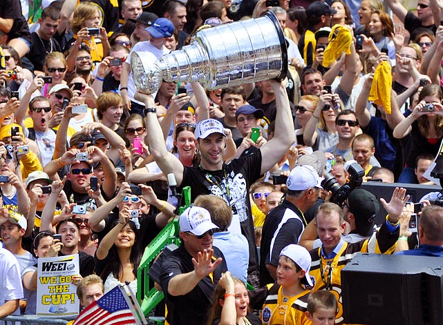 Boston Bruins defenseman Zdeno Chara proudly displays the city of Boston's seventh championship trophy since 2002 during the Bruins' victory parade on June 18.