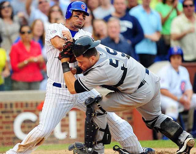 Chicago Cubs first baseman Carlos Pena (left) collides with New York Yankees catcher Russell Martin in the sixth inning of the Yankees' 4-3 victory on June 18. Despite the contact, Martin maintained control of the ball for the out. For more home plate collisions click  here .