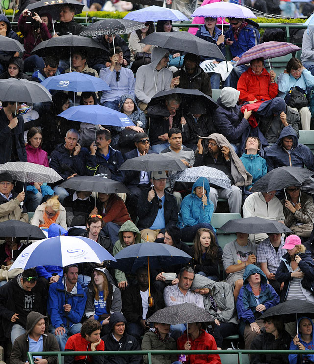 Spectators use umbrellas as the rain starts to fall.