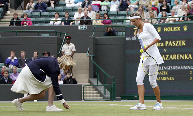 Victoria Azarenka of Belarus looks on as the umpire checks the moisture level of the grass.