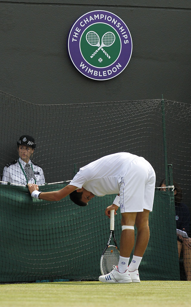 Serbia's Novak Djokovic rests on the edge of the court during his quarterfinal match against Australia's Bernard Tomic.