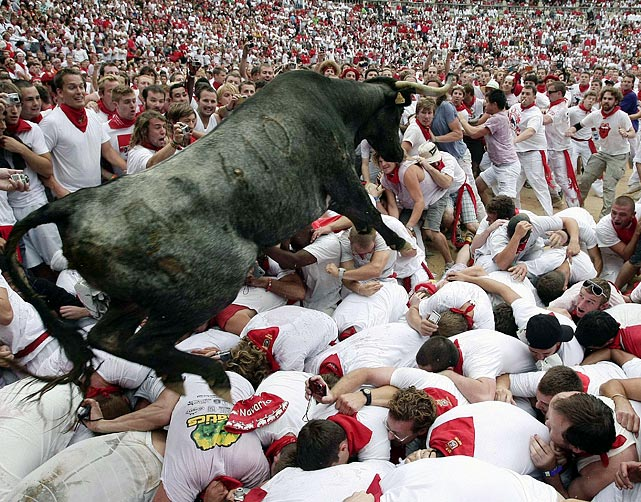 Revelers in Pamplona's annual Running of the Bulls crouch at the gate as a newly released bull jumps over them. The horns are covered during the seven-day festival.