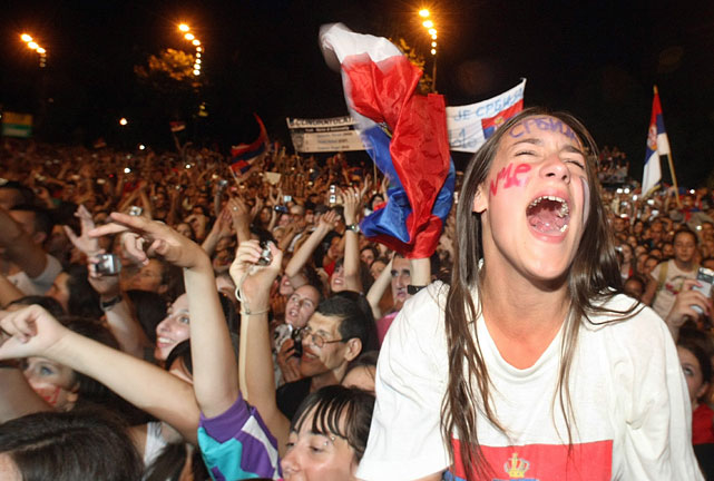 Fans celebrate and wave Serbian flags at Monday's welcoming ceremony.