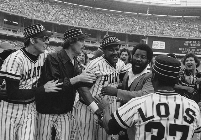Relief pitcher Kent Tekulve, left, and starter Bruce Kison, second from left, try to embrace Stargell after he hit his 32nd home run of the year against the Cubs to wrap up the NL East title for the Pirates in 1979. The pinstripe unis would be retired after that season.