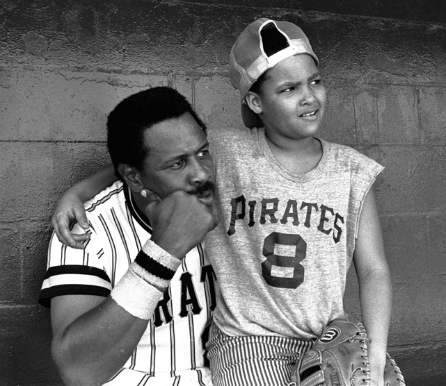 "A year before the Pirates adopted the ""We are Family"" moniker, Stargell sits in the dugout with his 10-year-old son during an exhibition game against the Phillies."