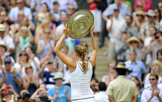 Petra Kvitova raises the trophy to the Centre Court audience.