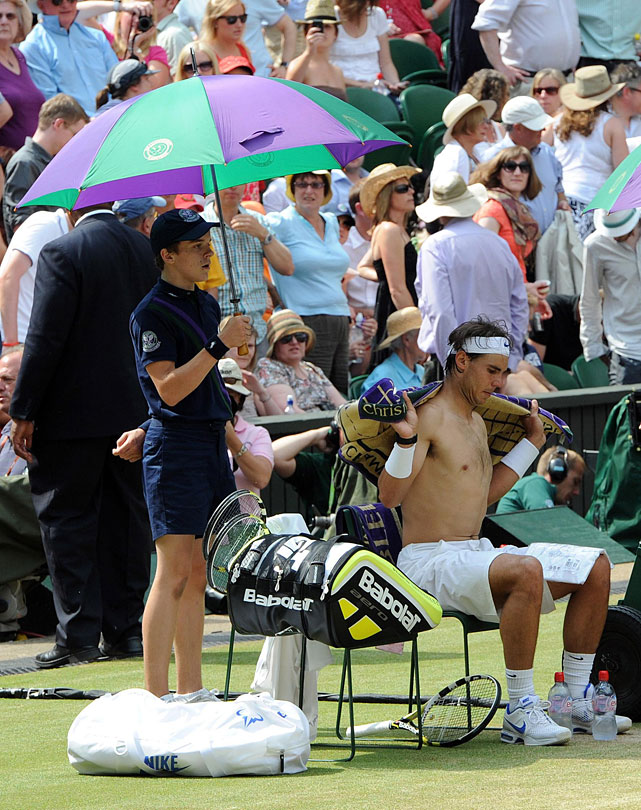 A ball boy holds an umbrella as Rafael Nadal changes his shirt.