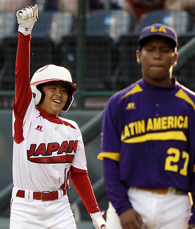 Japan's Gaishi Iguchi reacts after hitting an RBI single as Venezuela's Neil Prieto reacts. Japan, the defending champion, faced Mexico in the international final.