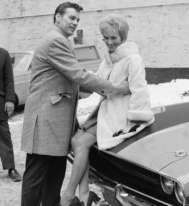 Len Dawson boosts his wife Jackie onto the hood of his new car in New York, which he received after being named the MVP of Super Bowl IV.  The couple were married from 1953 to Jackie's death in 1978.