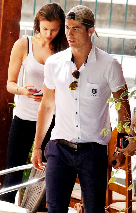 Cristiano Ronaldo rocks the casual but cool look, and the woman behind him complements him well.