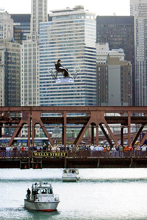 "Mario Wallenda, also of the Flying Wallendas, rides his specially constructed ""skycycle"" across the Chicago River in downtown Chicago. The 60-something Wallenda has been in a wheelchair since a high-wire accident in 1962 left him paralyzed from the waist down."
