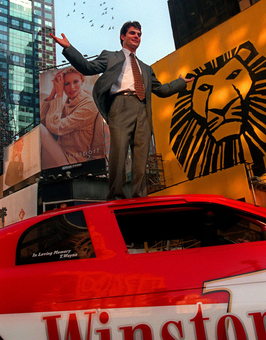 Jeff Gordon celebrates winning his third Winston Cup by standing atop his car in Times Square as part of the lead-up to the 1998 NASCAR annual awards show.