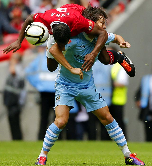 Manchester United's Patrice Evra gets tangled with Manchester City's David Silva while fighting for the ball during a FA Community Shield soccer match. Manchester United won 3-2.