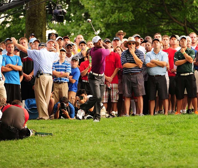 Tiger Woods knocks one out of the rough during the 16th hole of the Bridgestone Invitational's first round.