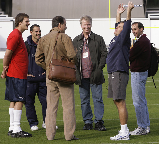 Belichick talks with former Giants quarterback Phil Simms and CBS broadcaster Jim Nantz as Tom Brady and others look on.