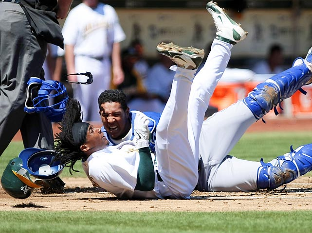 Helmets, a face mask, sunglasses and dreads go flying as the Oakland Athletics Jemile Weeks (bottom) collides with with Kansas City Royals Salvador Perez.