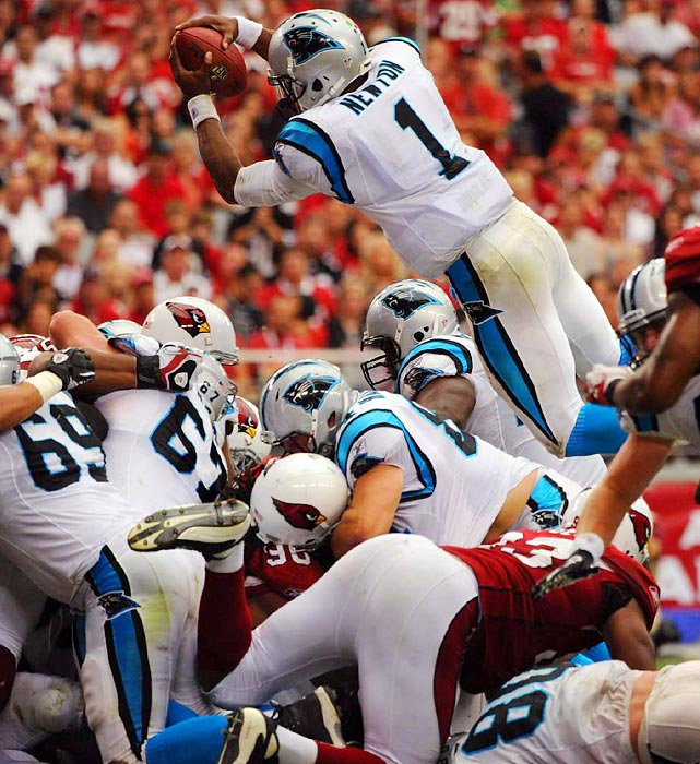 Cam Newton soared over the goal line, and into record books during his first NFL career game. Newton passed for 422 yards, threw two touchdowns and ran for one (shown here) and had only one interception, becoming the first rookie QB to throw for 400 yards in his debut.