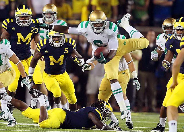 Notre Dame's Theo Riddick breaks free of a tackle during the first night game ever at the Big House (thanks to newly-installed stadium lights). Riddick caught six passes for 62 yards and two touchdowns, but even that wasn't enough to overcome the Wolverines, who scored the winning TD with two seconds remaining.