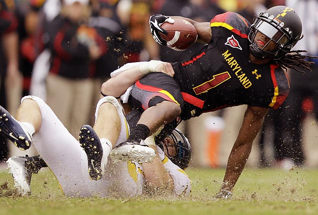 Maryland wideout Tony Logan slides across the wet grass at Byrd Stadium as he is tackled by West Virginia linebacker Jared Barber. Barber and the Mountaineers earned a 37-31 conference victory on the road.
