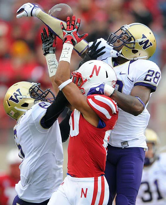 Nebraska wide receiver Kenny Bell (red) is sandwiched between two Washington cornerbacks. Quinton Richardson (28) is able to break up the pass, but the Cornhuskers came out on top 51-38 to remain unbeaten.