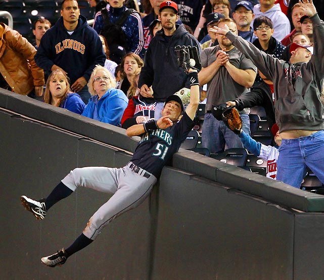 Seattle right fielder Ichiro Suzuki robs a fan of a souvenir with this diving catch on a foul ball hit by Twins' outfielder Michael Cuddyer.