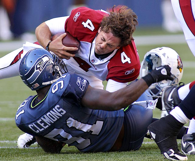 Arizona quarterback Kevin Kolb loses his headgear but hangs onto the football after he's sacked by Seattle's Chris Clemons.
