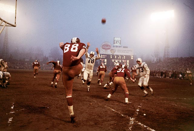 Redskins punter Pat Richter (#88) booms a kick out of his end zone and into the evening mist as his teammates head upfield to make the tackle.