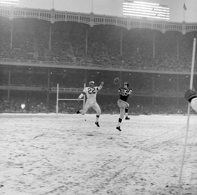 Silhouette against the Snowy Stadium, Giants receiver Bob Schnelker (#85) outleaps Browns defender Ken Konz to catch the pass.