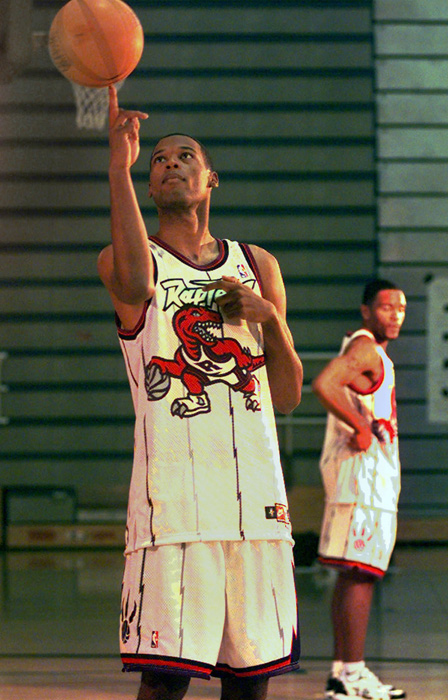 Marcus Camby shows off the Raptors' imposing dinosaur while spinning a basketball on his finger during the Raptors' 1997 training camp.