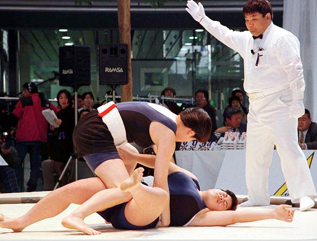 Female sumo wrestlers roll on the ground as a seemingly-indifferent judge watches over them.