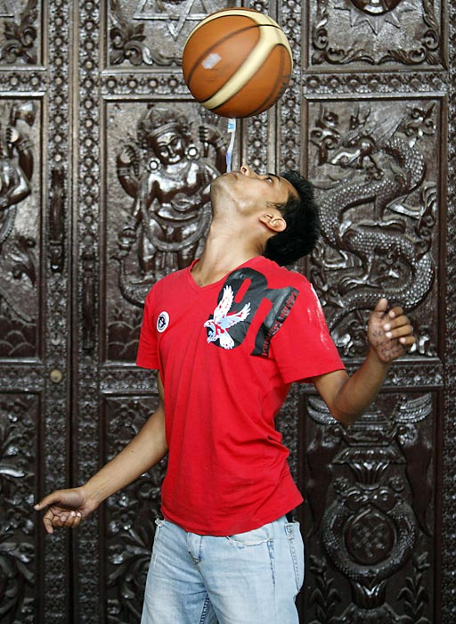 Thaneshwar Guragai, in Kathmandu, spins a basketball on a toothbrush while holding the toothbrush in his mouth for exactly 22.41 seconds to break the record of 13.5 seconds.