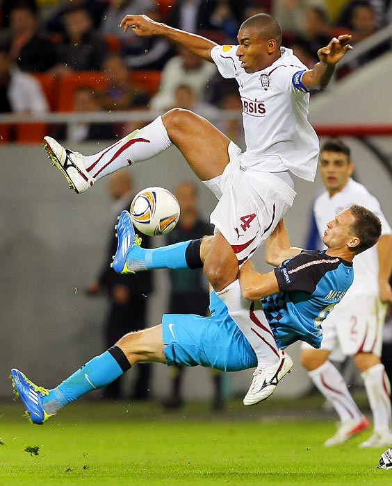 Tim Matavz of PSV Eindhoven falls while defending Marcos Antonio of Rapid Bucharest during a UEFA Europa League match.