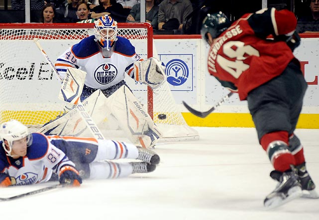 Minnesota Wild left wing Guillaume Latendresse shoots over Edmonton defenseman Taylor Fedun. Oilers' goalie Nikolai Khabibulin would make the save.