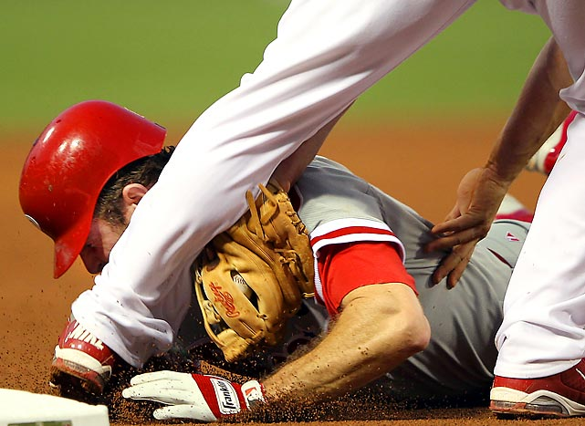 Phillies second baseman Chase Utley gets a taste of baseball glove as he's tagged out by David Freese of the St. Louis Cardinals in Game 4 of their divisional series.