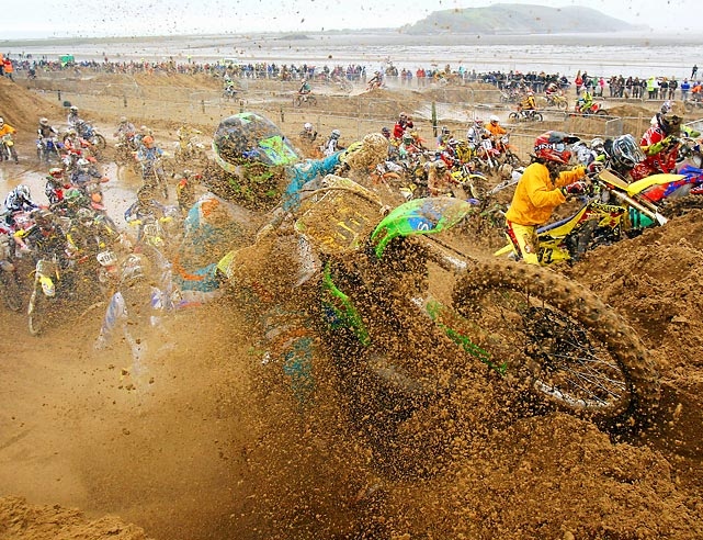 Motocross competitors get a little muddy attempting to clear a jump during the RHL Beach Race in England.