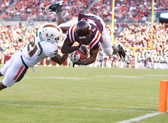 Hokies running back David Wilson (4) dives into the end zone against the Miami Hurricanes. Defensive back Brandon McGee (21) couldn't stop Wilson from helping his team to a 38-35 win.