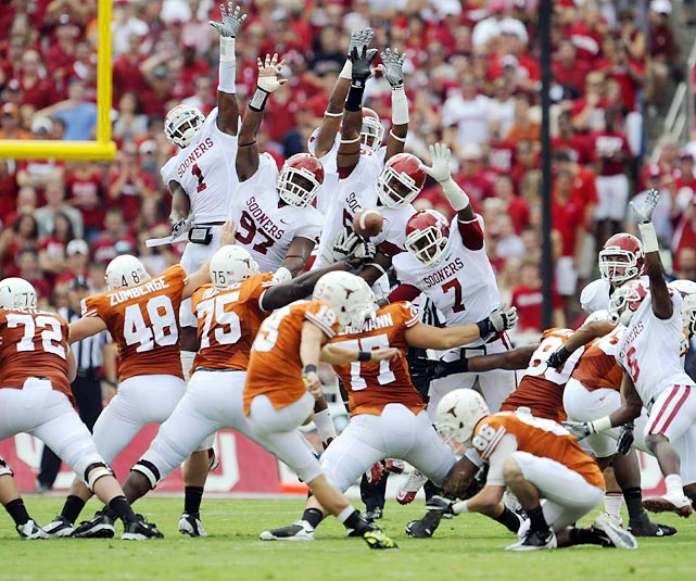 Texas kicker John Tucker somehow gets this kick past a wall of Sooners but Oklahoma got the best of this Red River Rivalry game with a 55-17 win.