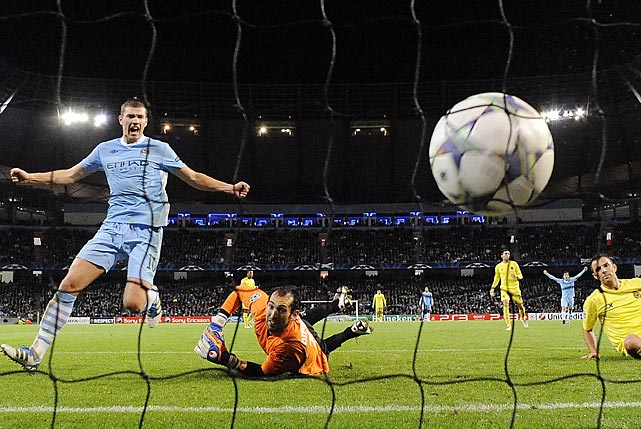 Villarreal's Carlos Marchena (right) scores an own goal past keeper Diego Lopez much to the delight of Manchester City's Edin Dzeko (left). Manchester City won 2-1.