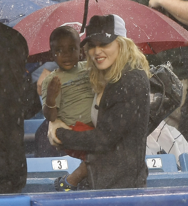 Madonna's night at the ballpark was soon ruined by the rain. In this photo, she tries to keep her son David dry as the duo is escorted out of the stadium.