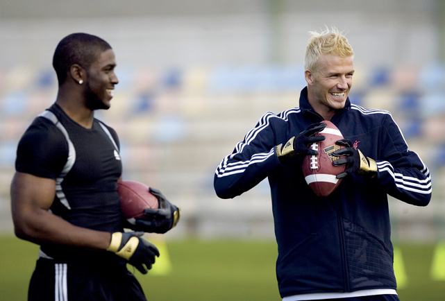 Beckham gives the other kind of football a try with Reggie Bush in Madrid, Spain.