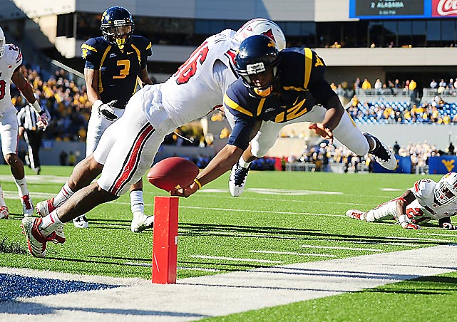 West Virginia quarterback Geno Smith can't get past Louisville linebacker Dexter Heyman to score a touchdown in Morgantown. Smith had three passing TDs in the Mountaineers 38-35 loss.
