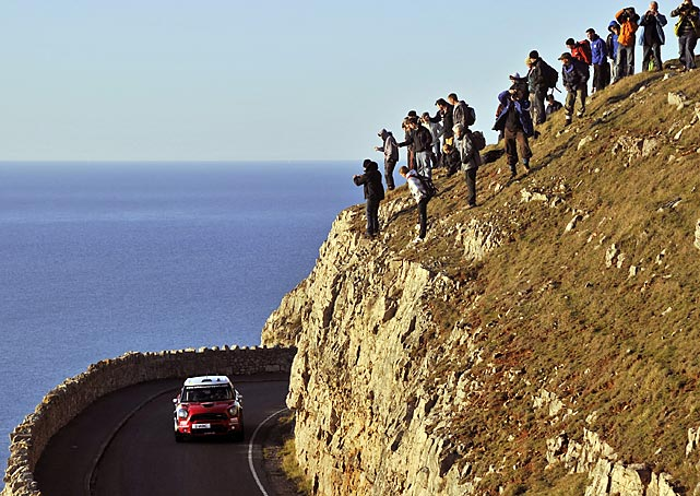Spectators watch Kris Meeke of Britain drive through Llandudno, UK, during the Wales Rally motorsport event.