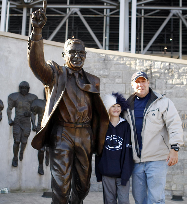 Fans pose next to a statue of Joe Paterno, who was not on the Penn State coaching staff vs. Nebraska for the first time since 1949.